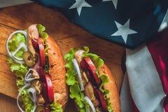 Dos perritos calientes frescos en un tablero de madera, los vidrios con cola y bandera americana fotografía de archivo libre de regalías