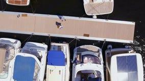 Dos personas adultas se colocan en el embarcadero del club náutico, tiroteo aéreo del abejón metrajes