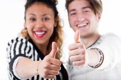 Dos personas alegres jovenes que dan los pulgares para arriba Fotografía de archivo libre de regalías