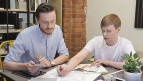 Dos personas del diseñador en la tabla que trabaja en la opción del color en la sala de estar almacen de metraje de vídeo