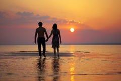 Dos personas en amor en la puesta del sol Foto de archivo libre de regalías