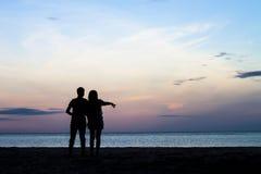 Dos personas en amor en la puesta del sol Imagen de archivo libre de regalías