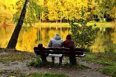 Dos personas en banco cerca del lago en día del otoño Imagen de archivo libre de regalías