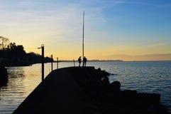 Dos personas en el muelle del lago Imagen de archivo libre de regalías