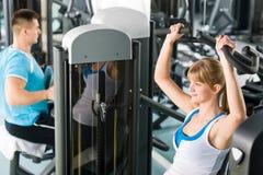 Dos personas en la máquina del ejercicio del centro de aptitud Imagen de archivo libre de regalías