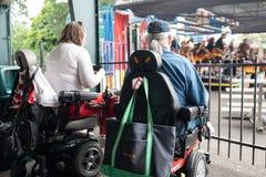 Dos personas en las sillas de ruedas que disfrutan del concierto del aire libre imagen de archivo libre de regalías