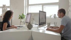 Dos personas están trabajando seriamente en el escritorio en ventana creativa de la oficina almacen de metraje de vídeo