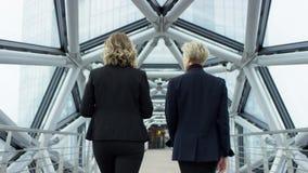 Dos personas femeninas de las empresarias caminan y discuten negocio Son todos que trabajan en distrito financiero central Son almacen de metraje de vídeo