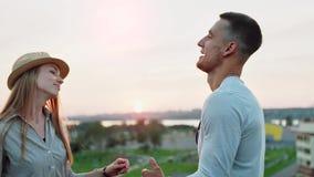 Dos personas jovenes de los estudiantes que bailan y que disfrutan de puesta del sol en el partido del tejado del verano almacen de video