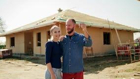 Dos personas jovenes delante de su nueva casa almacen de metraje de vídeo