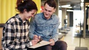 Dos personas jovenes disfrutan de su tiempo junto, dibujando algo en libreta Dentro, cantidad de la cámara lenta almacen de metraje de vídeo