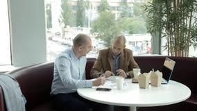 Dos personas jovenes en el almuerzo en un café por los tallarines de consumición del café y de la consumición de la ventana que d almacen de metraje de vídeo