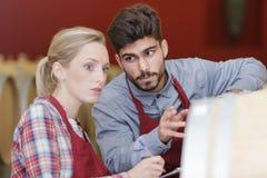 Dos personas jovenes en la bodega que hace notas en el tablero fotos de archivo