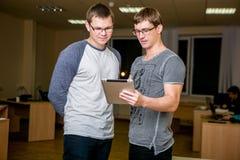 Dos personas jovenes están discutiendo un proyecto en la oficina Colocándose uno al lado del otro, uno de ellos dice el otro sobr foto de archivo
