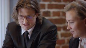 Dos personas jovenes están trabajando juntas y están discutiendo proyectos en un café La mujer y el hombre en un restaurante o almacen de metraje de vídeo
