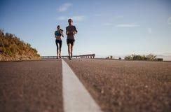 Dos personas jovenes que corren en la carretera nacional Foto de archivo