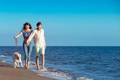 Dos personas jovenes que corren en la playa que se besa y que se sostiene firmemente con el perro Fotos de archivo