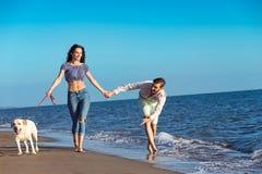 Dos personas jovenes que corren en la playa que se besa y que se sostiene firmemente con el perro Imagen de archivo