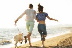 Dos personas jovenes que corren en la playa que se besa y que se sostiene firmemente con el perro Imagen de archivo libre de regalías