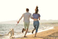 Dos personas jovenes que corren en la playa que se besa y que se sostiene firmemente con el perro Imágenes de archivo libres de regalías