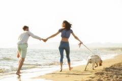 Dos personas jovenes que corren en la playa que se besa y que se sostiene firmemente con el perro Imagenes de archivo
