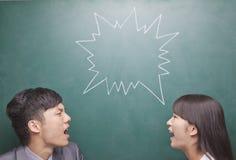 Dos personas jovenes que gritan en uno a delante de la pizarra, símbolo en la pizarra Foto de archivo