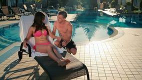 Dos personas jovenes que hablan cerca de la piscina almacen de metraje de vídeo