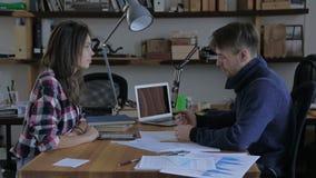 Dos personas jovenes que hablan delante de uno a en un escritorio en la oficina almacen de video