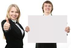 Dos personas jovenes que llevan a cabo una muestra blanca Fotografía de archivo