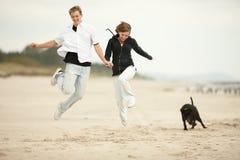 Dos personas jovenes que saltan en la playa y sostenerse Fotografía de archivo libre de regalías