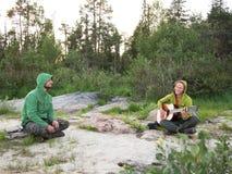 Dos personas jovenes que se sientan en la tierra Foto de archivo libre de regalías
