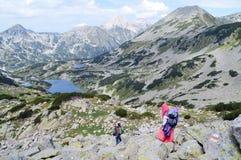Dos personas jovenes que suben abajo en bazofia pedregosa de la montaña Fotos de archivo libres de regalías
