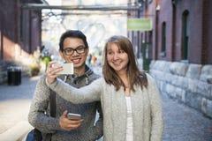 Dos personas jovenes que toman un selfie con smartphone Imagen de archivo