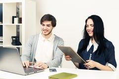 Dos personas jovenes que trabajan así como el ordenador portátil y la tableta mientras que se sienta en la oficina blanca minimal Imagen de archivo