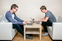 Dos personas jovenes que trabajan en los ordenadores portátiles en la oficina, escribiendo un programa, corrigiendo el texto fotografía de archivo libre de regalías