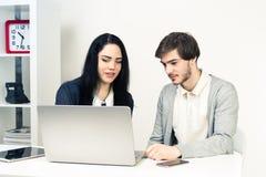 Dos personas jovenes que trabajan junto mientras que se sienta en la oficina blanca minimalistic Foto de archivo