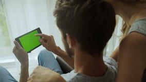 Dos personas jovenes que usan la tableta en hogar almacen de video