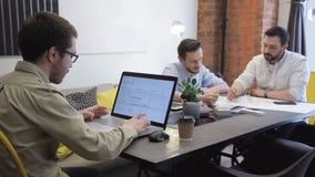 Dos personas jovenes ven la hoja de papel con el dibujo en oficina almacen de metraje de vídeo