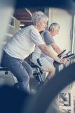 Dos personas mayores que se resuelven en la máquina elíptica Fotografía de archivo