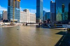 Dos personas montan el río Chicago en una canoa temática americana irlandesa, con el horizonte de Chicago y la construcción de ra imagen de archivo libre de regalías