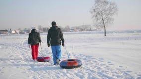 Dos personas montan en una colina nevosa en un trineo Un hombre y una muchacha suben al top de la montaña Paseos en el aire fresc almacen de metraje de vídeo