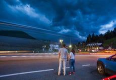 Dos personas pares que llevan a cabo las manos en las nubes de tormenta imagen de archivo