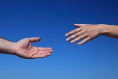 Dos personas que alcanzan las manos Imágenes de archivo libres de regalías