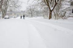 Dos personas que caminan abajo de una carretera nacional en ventisca asaltan Imagen de archivo libre de regalías