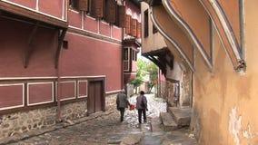 Dos personas que caminan abajo en una calle vieja de Plovdiv Bulgaria metrajes