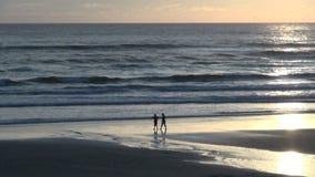 Dos personas que caminan a lo largo de orilla en la playa del cañón almacen de metraje de vídeo