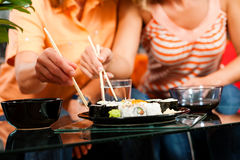 Dos personas que comen el sushi Imagenes de archivo