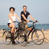 Dos personas que completan un ciclo en la costa Imagen de archivo libre de regalías