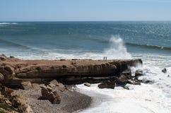 Dos personas que consiguen mojadas de chapoteo del agua en la costa costa marroquí imagen de archivo