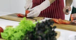 Dos personas que cortan los tomates inkitchen metrajes